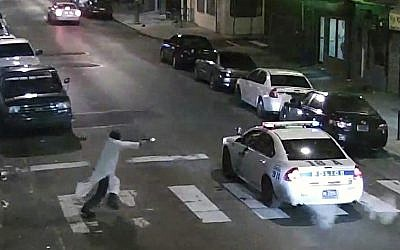 In this frame from a Thursday, Jan. 7, 2016 video provided by the Philadelphia Police Department, Islamic State-inspired Edward Archer, 30, runs with a gun toward a police car driven by Officer Jesse Hartnett, 33, in Philadelphia. (Philadelphia Police Department via AP)