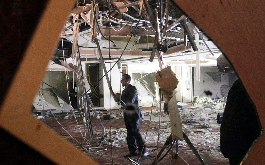 A Jordanian official is reflected in a broken mirror at the devastated site of the wedding hall at the Radisson SAS Hotel, where one of the three bombings took place in Amman, Jordan, in November 2005. (AP/Amr Nabil)