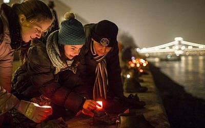 File: Backdropped by the illuminated Chain Bridge, people light candles in front of the cast iron shoes at the Holocaust Memorial on the quay of the River Danube, during International Holocaust Remembrance Day in Budapest, Hungary, Wednesday, Jan. 27, 2016. (Balazs Mohai/MTI via AP)