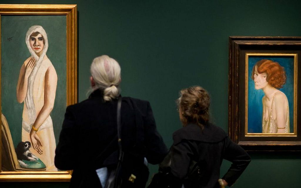 Visitors viewing Max Beckmann's 'Portrait Quappi Beckmann,' from 1925, at the Hypo-Kunsthalle in Munich, Germany, April 10, 2014. (Joerg Koch/Getty Images/via JTA)