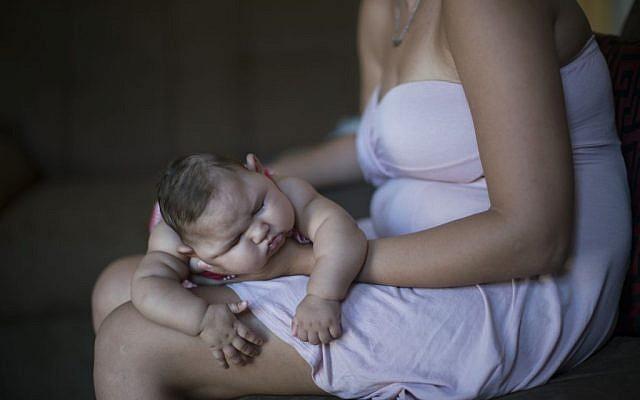 Gleyse Kelly da Silva holds her daughter Maria Giovanna as she sleeps in their house in Recife, Pernambuco state, Brazil, Wednesday, Jan. 27, 2016. (AP Photo/Felipe Dana)