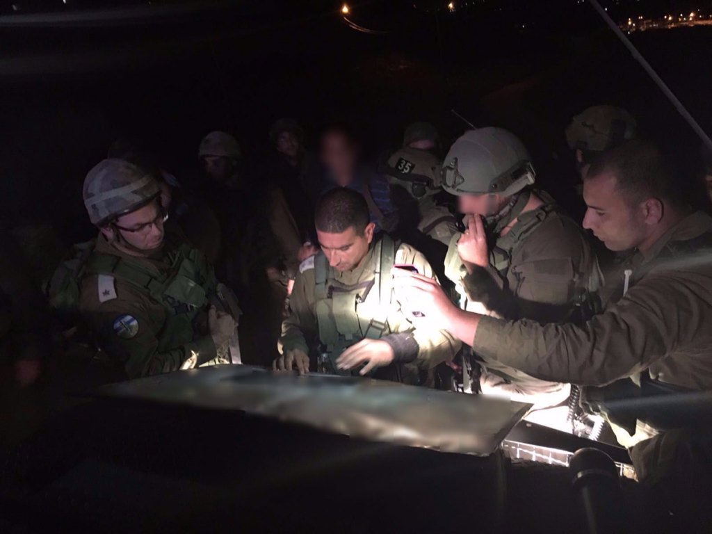 Col. Yariv Ben-Ezra, commander of the IDF's Judea Regional Brigade, works with his officers in the field as they search for the man who stabbed and killed an Israeli woman in her home in the Otniel settlement in the West Bank on January 17, 2016. (IDF Spokesperson's Unit)