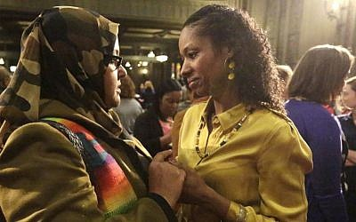 Wheaton College professor Larycia Hawkins, right, is greeted by supporter Donna Demir after a news conference Wednesday, Jan. 6, 2016, in Chicago. (AP Photo/M. Spencer Green)