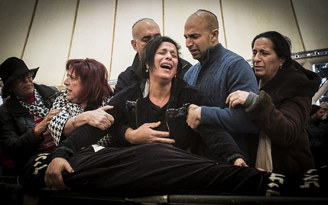Family and friends of Alon Bakal cry at his funeral in the northern Israeli city of Carmiel on January 3, 2015. (Basel Awidat/Flash90)