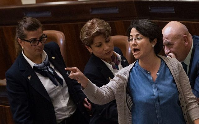 MK Hanin Zoabi being escorted out of the plenary hall by security guards after interrupting an assembly session in the Israeli Knesset, June 17, 2015. (Miriam Alster/Flash90)