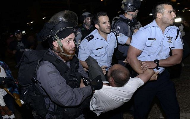 An Ethiopian Israeli is detained by police officers during a protest march in Rabin Square, Tel Aviv, June 22, 2015.