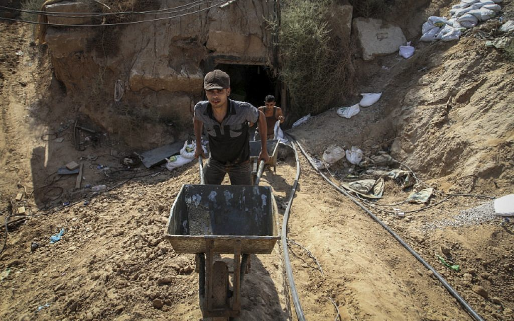 File: Palestinian men work at the entrance of a tunnel used for smuggling supplies between Egypt and the Gaza Strip after being flooded with seawater by the Egyptian army, in Rafah in southern Gaza on October 1, 2015. (Abed Rahim Khatib/ Flash90)