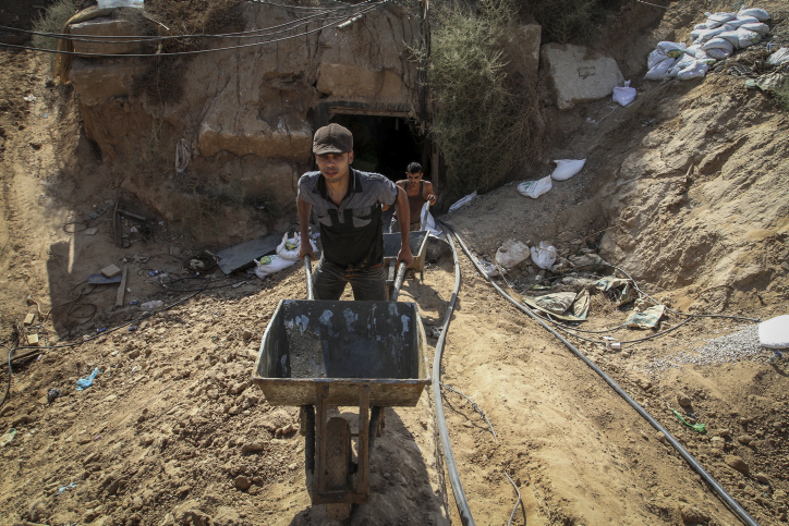 Palestinian men work at the entrance of a tunnel used for smuggling supplies between Egypt and the Gaza Strip after being flooded with seawater by the Egyptian army, in Rafah in southern Gaza on October 1, 2015. (Abed Rahim Khatib/ Flash90)