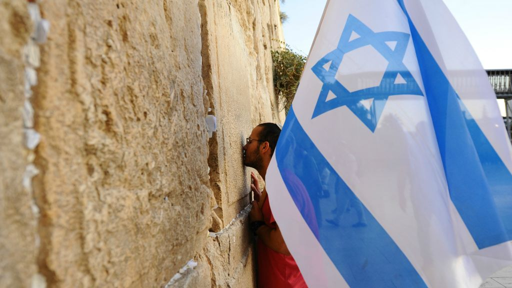 A man holds an Israeli flag during a march in support of the city of Jerusalem at the Western Wall, in Jerusalem's Old City on October 22, 2015, following a wave of terror attacks. (Mendy Hechtman/Flash90)