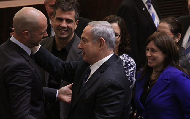 New Likud MK Amir Ohana is congratulated after his swearing-in during a plenum session in the Israeli parliament, on December 28, 2015. (Isaac HArari/FLASH90)