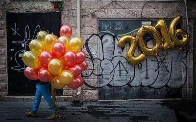 """A man walks with balloons past a festive """"2016"""" balloon display on New Year's Eve in central Jerusalem, December 31, 2015. (Hadas Parush/Flash90)"""