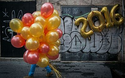 "A man walks with balloons past a festive ""2016"" balloon display on New Year's Eve in central Jerusalem, December 31, 2015. (Hadas Parush/Flash90)"