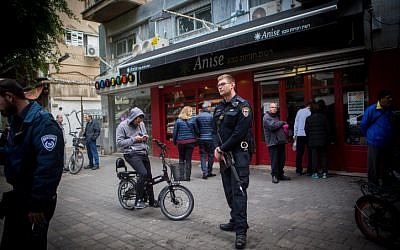 Police officers stand outside a bar on Dizengoff Street  in central Tel Aviv, on January 2, 2016, a day after two people were killed in a shooting there. Visible in the image is the adjacent Anise health foods store, where the shooter abandoned his backpack as he launched his attack. (Miriam Alster/Flash90)