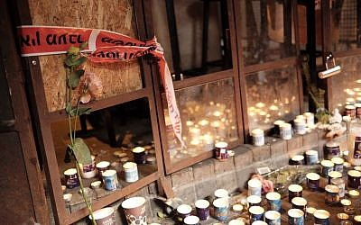 Israelis light candles outside a cafe in Tel Aviv, on January 2, 2016, a day after two people were killed in a shooting there (Tomer Neuberg/Flash90)