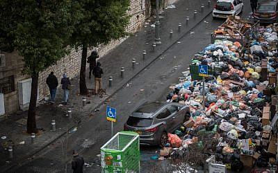 People walk next to a pile of uncollected garbage in downtown Jerusalem on January 3, 2016, on the fourth day of a strike by the city's sanitation workers. (Hadas Parush/Flash90)