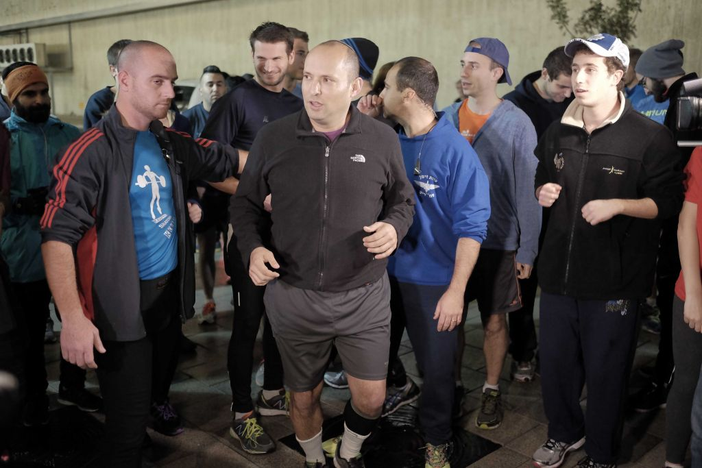 Naftali Bennett runs in in central Tel Aviv on January 3, in a show of solidarity two days after a deadly shooting attack on Dizengoff Street, and with the gunman still at large. (Tomer Neuberg/Flash90)
