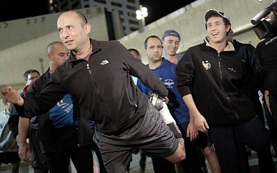 Education Minister Naftali Bennett warms up before a night run in central Tel Aviv on Monday, January 4, 2016, in a bid to inspire courage in the hearts of the city's residents two days after a deadly shooting attack (Tomer Neuberg/Flash90)