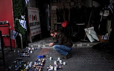 Israelis light memorial candles outside the pub on Dizengoff Street in central Tel Aviv on January 4, 2016, several days after two people were killed, and seven were injured, in a shooting at the bar on January 1, 2016. (Ben Kelmer/Flash90)
