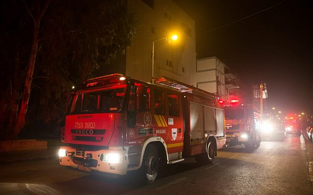 Firefighting teams work to put out a fire at the building where the offices of the human rights NGO B'Tselem are located, in Jerusalem on January 10, 2016. Police were investigating whether it was arson. (Yonatan Sindel/Flash90)