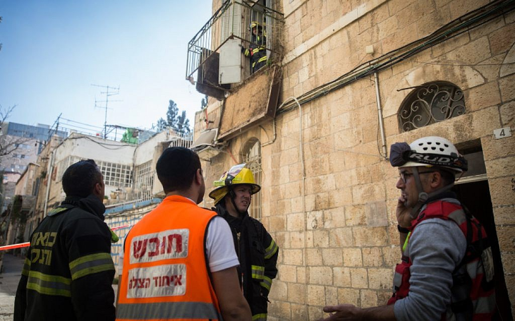 Firefighters at the scene where an apartment balcony collapsed, in central Jerusalem, on January 12, 2016. (Hadas Parush/Flash90)