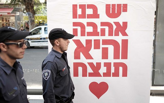 Police officers stand by a poster reading: 'We have love in us, and it will win,' at a street party on January 15, 2016 at the Simta bar in Tel Aviv, where two weeks ago two Israelis were killed in a shooting attack. (Photo by Tomer Neuberg/FLASH90)
