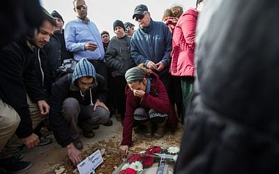 People mourn over the fresh grave of Dafna Meir, during her funeral in Jerusalem on January 18, 2016. (Yonatan Sindel/Flash90)