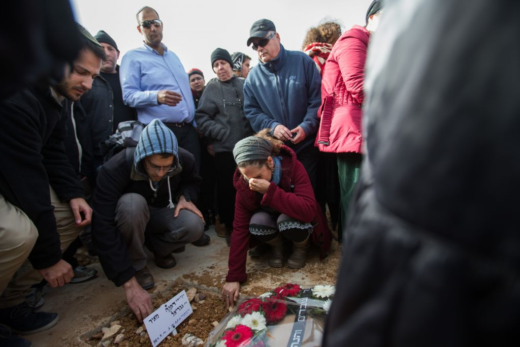 People mourn over the fresh grave of Dafna Meir, during her funeral in Jeursalem on January 18, 2016. (Yonatan Sindel/Flash90)
