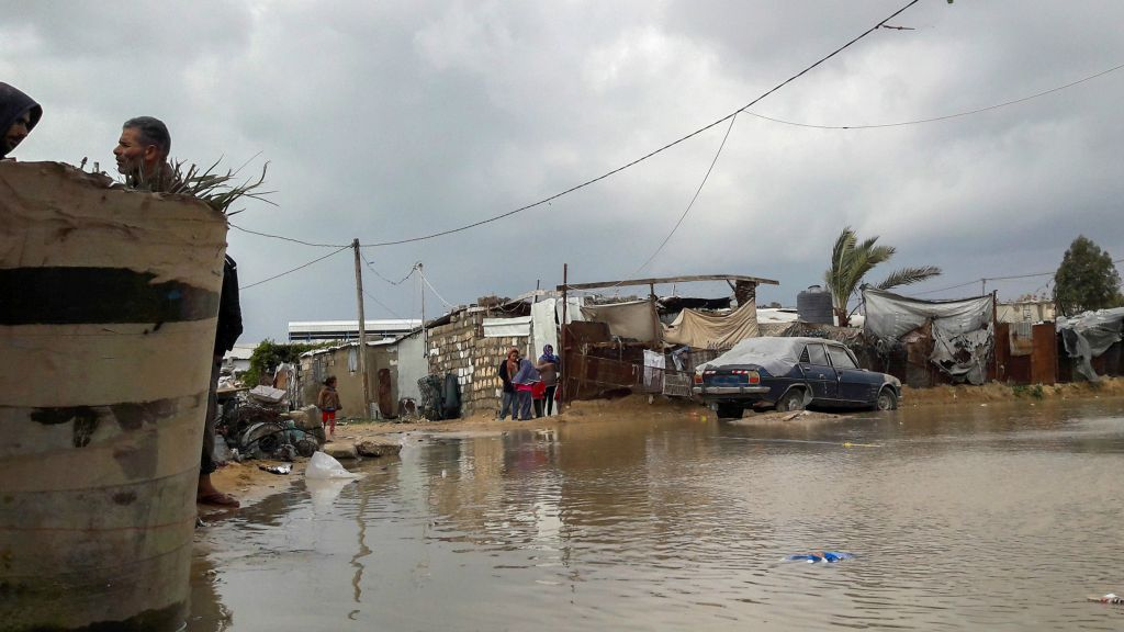 Palestinians stand near a road flooded with rainwater following heavy rains, in Khan Younis in the southern Gaza Strip on January 24, 2016. (Abed Rahim Khatib/Flash90)