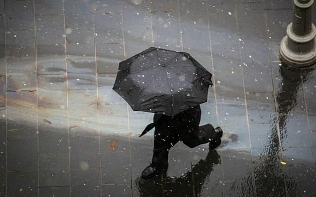 People walk with umbrellas in central Jerusalem as light snow begins to fall, January 25, 2016. (Hadas Parush/Flash90)