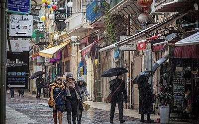People walk on Nahalat Shiva Street in central Jerusalem on January 25, 2016, as light snow begins to fall, with a chance of heavy snow coming later. (Hadas Parush/Flash90)