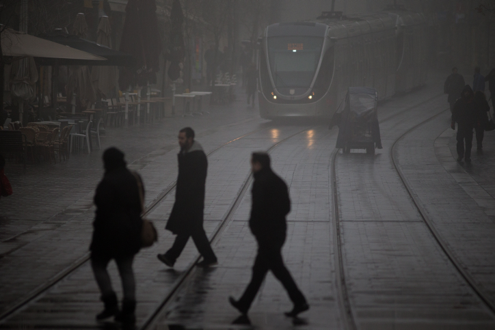 Israelis walk across the lightrail tracks on Jaffa road in Jerusalem on January 26, 2016, (Yonatan Sindel/Flash90)