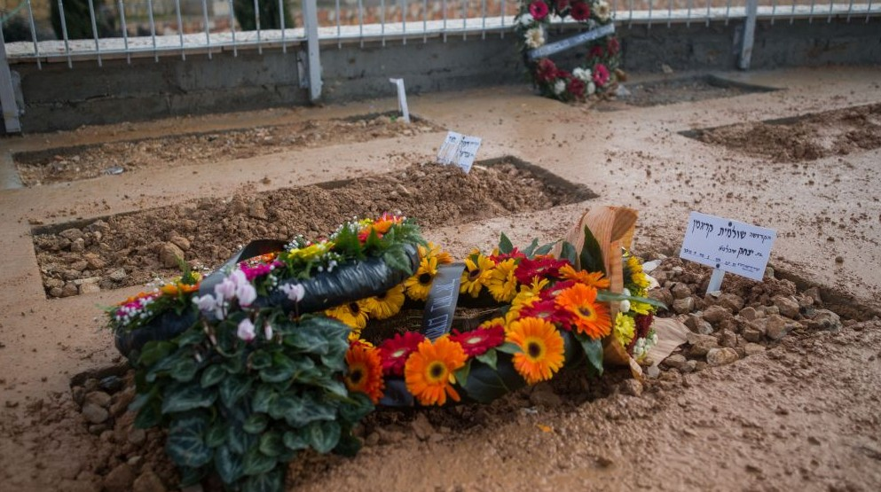 The fresh grave of Shlomit Krigman, 23, at Har Hamenuhot cemetery in Jeursalem on January 26, 2016, shortly after her funeral. The next grave over is that of Dafna Meir (Yonatan Sindel/Flash90)