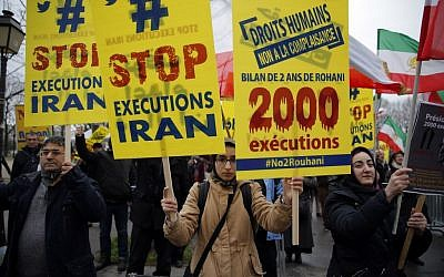 Supporters of the National Council of Resistance of Iran,demonstrate against the Iranian President Hassan Rouhani's visit to Paris,  Jan. 28, 2016. (AP Photo/Christophe Ena)