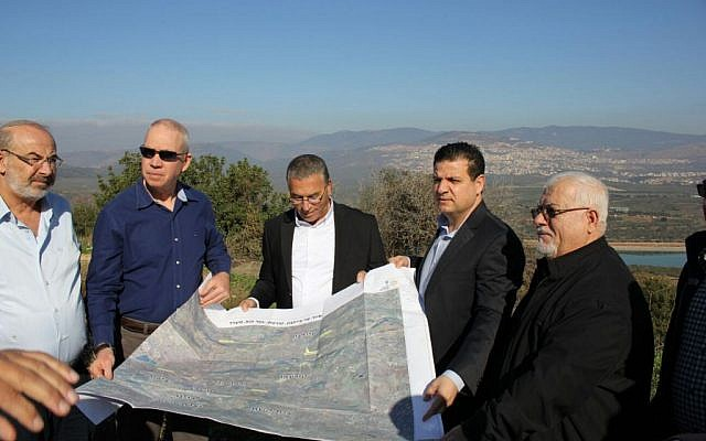 Housing Minister Yoav Gallant (second from left) and MK Ayman Odeh (second from right) stop at Eilabun, a village 15 kilometers (9 miles) south-west of Safed, during a tour of Arab villages in the Galilee, January 12, 2016. (Courtesy)