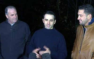 In this image made from video, former U.S Marine Amir Hekmati, center, is flanked by Michigan congressman Dan Kildee, left, and Hekmati's brother-in-law Ramy Kurdi as he speaks to the media  in Landstuhl, Germany, Tuesday, Jan. 19, 2016. (APTN via AP)