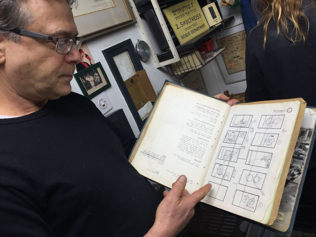 Rafi Kishon looking at one of his father's notebooks, with pages covered in story notes and story boards (Jessica Steinberg/Times of Israel)