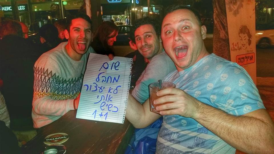 """Patrons at Ilka Bar sit with their drinks and a sign that reads: """"No terrorist will stop me when there's 1+1"""" (Courtesy Ilka Bar)"""