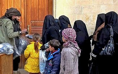 In this photo released on Jan. 31, 2014 by a militant website, members of the Islamic State group, left, distribute niqabs, enveloping black robes and veils that leave only the eyes visible, to Iraqi women in Mosul, northern Iraq. (Militant website via AP, File)