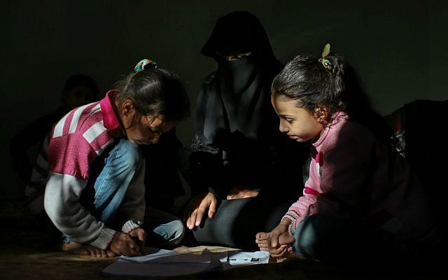In this Dec. 6, 2015, photo, Syrian refugee children Nahlah, left, and Nour, from the central Syrian city of Palmyra, play in the Turkish town of Reyhanli. (AP Photo/Emrah Gurel)