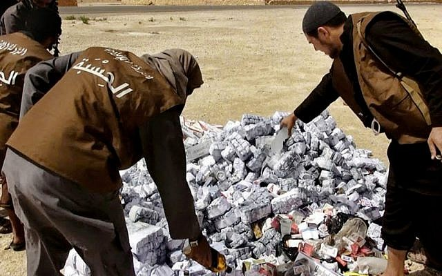 In this file photo released on May 3, 2015 by a militant website, members of the Islamic State group's vice police known as Hisba prepare to burn cigarettes and alcohol, in Homs Province, Syria. (Militant website via AP, File)