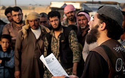 In this file photo released on May 14, 2015, by a militant website, a member of the Islamic State group's vice police known as 'Hisba' reads a verdict handed down by an Islamic court in Raqqa, Syria, sentencing many they accused of adultery to lashing (Militant website via AP, File)