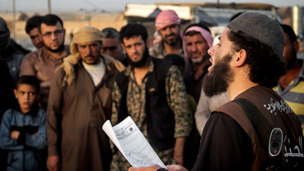"""In this file photo released on May 14, 2015, by a militant website, a member of the Islamic State group's vice police known as """"Hisba"""" reads a verdict handed down by an Islamic court in Raqqa, Syria, sentencing many they accused of adultery to lashing. A Hisba member """"must be gentle and pleasant toward those he orders or reprimands,"""" says an IS document obtained by the AP. Yet, escaped Syrians complain of the cruelty of the Hisba. (Militant website via AP, File)"""