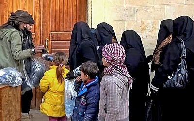 Members of the Islamic State group distribute niqabs and veils to Iraqi women in Mosul, northern Iraq, January 31, 2014. (Militant website via AP, File)