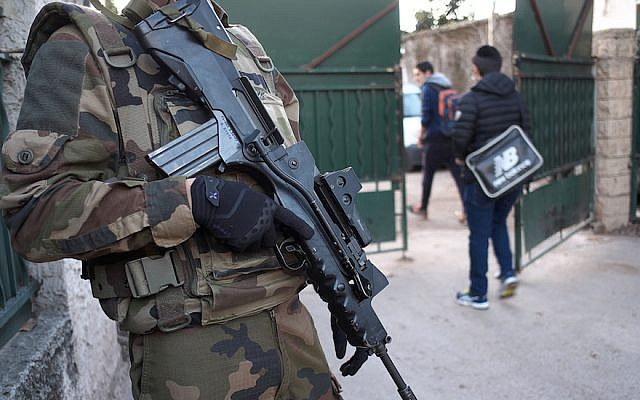 An armed French soldier securing the access to the La Source Jewish school in Marseille, southern France a day after a teenager, armed with a machete and a knife, wounded a teacher slightly before being stopped and arrested, Jan. 12, 2016. (Boris Horvat/AFP/Getty Images, via JTA)