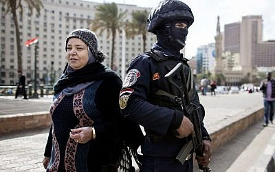 A woman walks past an Egyptian policeman, a day ahead of the fifth anniversary of the Jan. 25, 2011 uprising in Tahrir Square, Cairo, Egypt on Jan. 24, 2016. (AP Photo/Roger Anis)