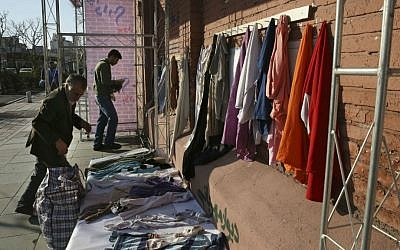 In this Thursday, Jan. 7, 2016 photo, Iranian men hang clothes on an outdoor charity wall in downtown Tehran, Iran. (AP Photo/Vahid Salemi)
