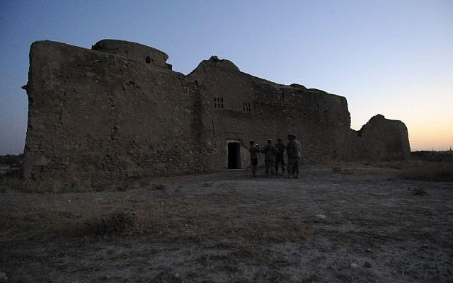 US soldiers stand at the entrance to the ruins of St. Elijah's Monastery after completing a tour there, at Forward Operating Base Marez in Mosul, Iraq, August 21, 2009.  (MC1 (SCW) Carmichael Yepez/U.S. Army via AP)