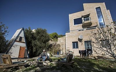 In this photo taken Sunday, Jan. 17, 2016, Moshe Gordon sits outside his guest house advertised on Airbnb international home-sharing site in Nofei Prat settlement at the West Bank. Palestinians say that by contributing to the settlement economy, Airbnb, like other companies doing business there, is perpetuating the expansion of Israel's settlement enterprise. The criticism puts the travel site in the crosshairs of a burgeoning boycott movement and highlights the intricacies of the sharing economy in a legal anomaly such as the settlements, where residents are Israeli citizens but the land is occupied. (AP Photo/Tsafrir Abayov)
