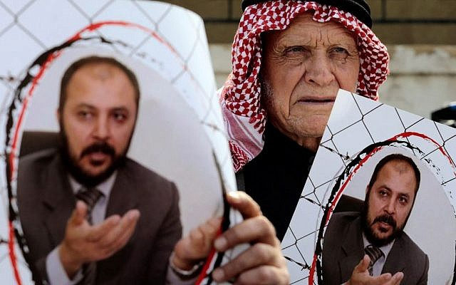 Supporters of Zaki Bani Irsheid, a top leader of the Muslim Brotherhood opposition group, hold photos of him, outside the state security court in Amman, Jordan, February 15, 2015. (AP Photo/Raad Adayleh)
