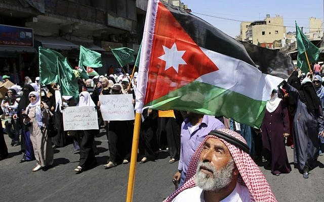 A Jordanian protester carries the national flag during a rally by the Muslim Brotherhood, in Amman, Jordan, July 31, 2015. (AP Photo/Raad Adayleh)